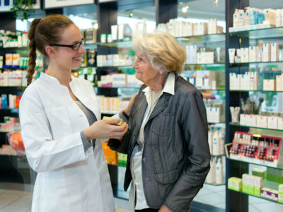 Pharmacist helping a grateful senior patient woman in the pharmacy.
